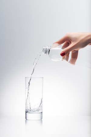 woman pouring water into glass from plastic bottle Standard-Bild