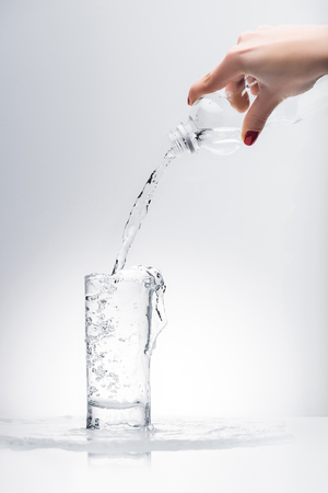 woman pouring water into glass from plastic bottle Stock Photo