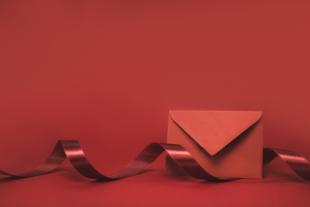 close up view of envelope and ribbon isolated on red