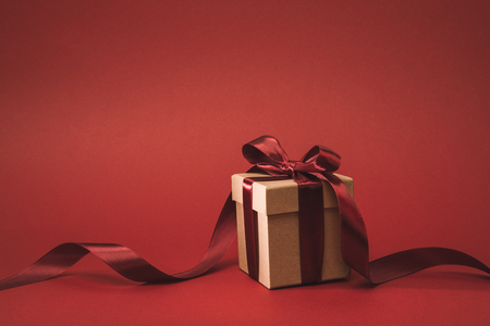close up view of present decorated with ribbon isolated on red Foto de archivo