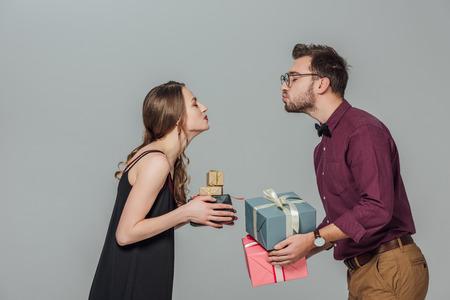vista laterale di giovani coppie felici che tengono i contenitori di regalo e capaci di baciare