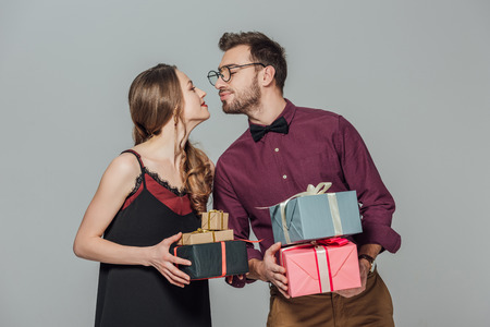 fashionable happy young couple holding gift boxes and able to kiss