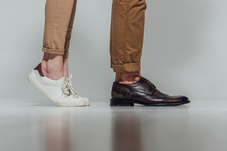 cropped shot of male and female legs in footwear with reflection Stock Photo