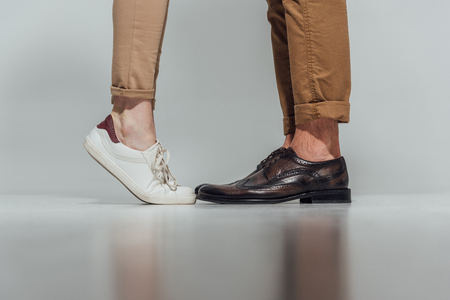 partial view of male and female legs in footwear with reflection