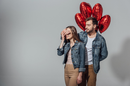 young man holding red heart shaped balloons and closing eyes to happy girlfriend