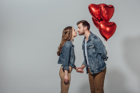 side view of young couple able to kiss while man holding red heart shaped balloons