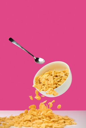 bowl with healthy tasty corn flakes and spoon on pink Imagens