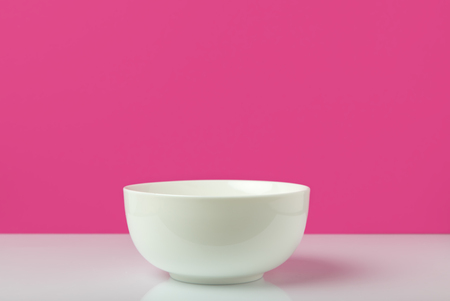 single empty white bowl ready for breakfast on pink Stock Photo