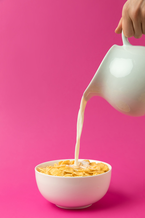 partial view of person pouring fresh healthy milk from jug into bowl with corn flakes 스톡 콘텐츠