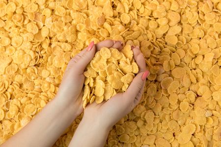 female hands holding crunchy tasty corn flakes