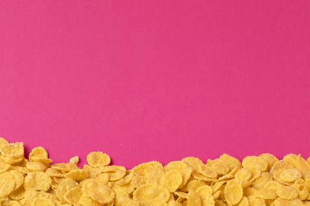 delicious crunchy corn flakes isolated on pink background Фото со стока