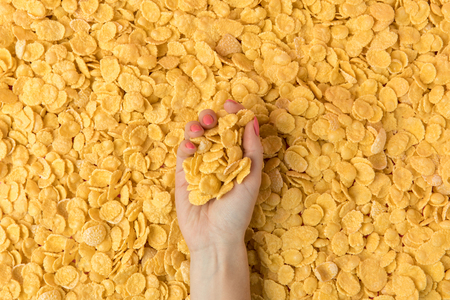 female hand holding crunchy organic corn flakes