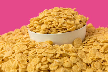 white bowl with tasty crispy corn flakes on pink