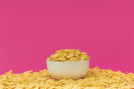 white bowl with tasty crispy corn flakes isolated on pink Фото со стока