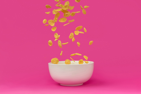 close-up view of delicious corn flakes falling into white bowl Imagens
