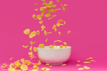 close-up view of delicious crunchy corn flakes falling into white bowl