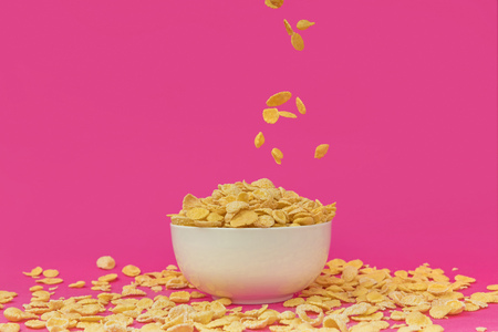 sweet healthy corn flakes falling into white bowl on pink Фото со стока