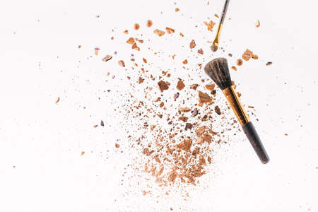 pieces of powder with makeup brushes falling Stock Photo