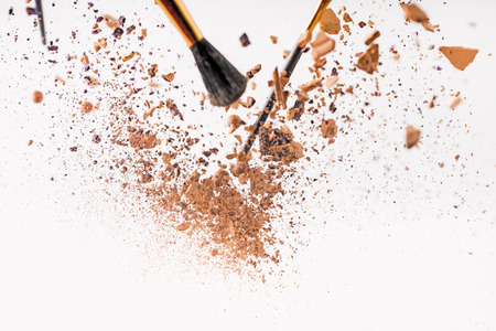 pieces of cosmetic powder with brushes falling Stock Photo