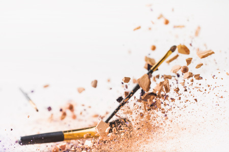 pieces of cosmetic powder with makeup brushes falling