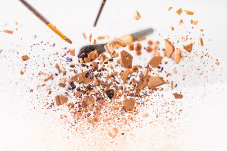 close-up shot of pieces of cosmetic powder with makeup brushes falling Stock Photo