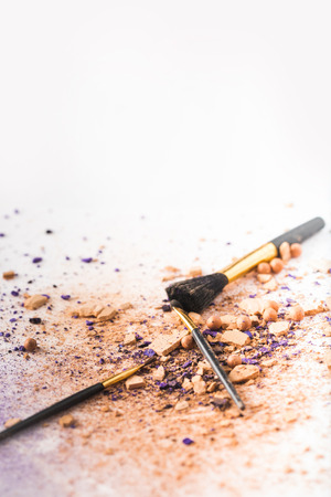 brushes lying on white surface spilled with cosmetic powder Stock Photo