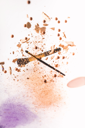 crushed cosmetic powder with makeup brushes falling