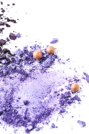 purple cosmetic eye shadows spilled on surface