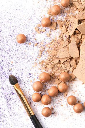 top view of crushed cosmetic powder with brush