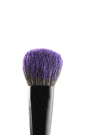 purple cosmetic powder on makeup brush