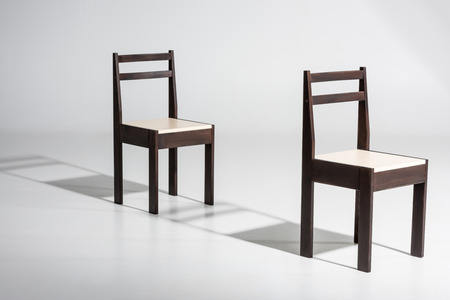 Two classic dark wooden chairs with white top standing in row on white floor in studio