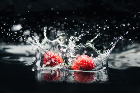 ripe strawberries falling in water