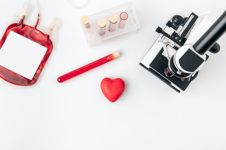 Coeur rouge contre flacons avec le sang et le microscope Banque d'images - 93600063