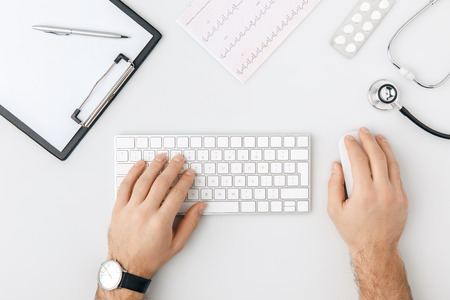 top view of hand with wristwatch on keyboard