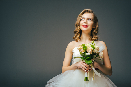 beautiful pensive bride with wedding bouquet looking away Stock Photo
