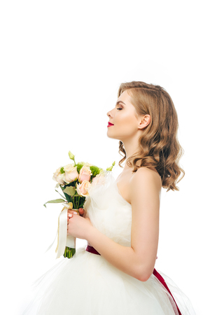 side view of bride in wedding dress with bouquet of flowers in hands Stock Photo