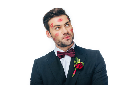 portrait of handsome groom in suit with red lipstick on face