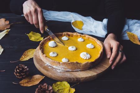 Female hands cutting pumpkin pie 版權商用圖片