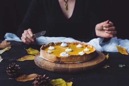 Pumpkin pie on table and woman with knife