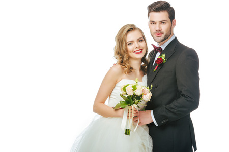 portrait of smiling bride with wedding bouquet and groom near by