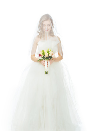 bride in wedding dress and veil with wedding bouquet in hands isolated on white