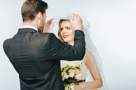 groom looking at beautiful bride in veil with bouquet of flowers