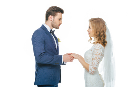 side view of beautiful wedding couple holding hands and looking at each other Stock Photo
