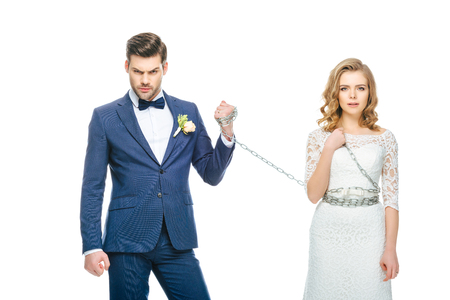 groom holding shocked young bride on chain