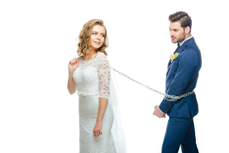 bride holding groom on chain isolated on white