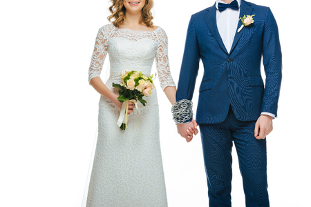 cropped shot of chained wedding couple holding hands