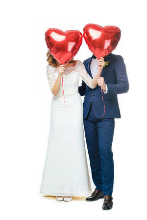 wedding couple covering faces with red heart shaped balloons
