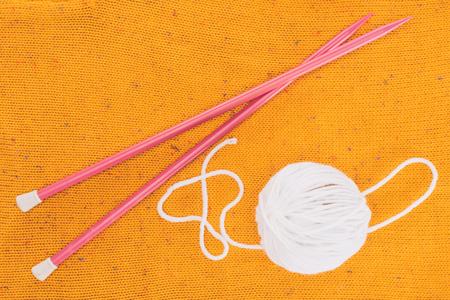원사 공 및 노란색 뜨개질에 뜨개질 바늘