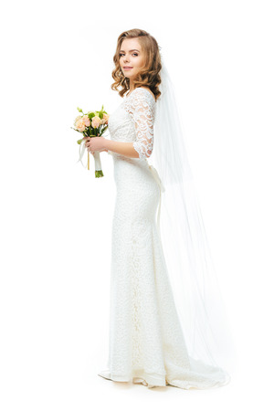 side view of attractive bride in wedding dress and veil with bouquet of flowers