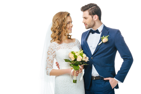 portrait of smiling bride with wedding bouquet and groom